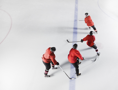 Hockey team in red uniforms skating on ice LANG_EVOIMAGES
