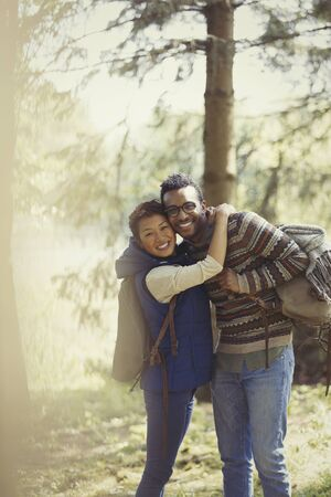 looking away from camera: Portrait smiling couple with backpacks hiking in woods