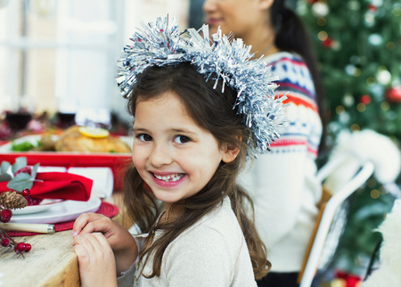 smile close up: Portrait enthusiastic girl wearing wreath at Christmas dinner LANG_EVOIMAGES