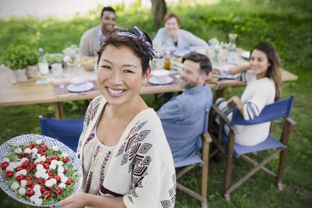 Portrait smiling woman serving Caprese salad to friends at garden party table