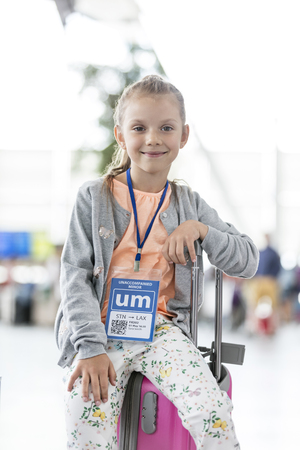 Portrait smiling girl sitting on suitcase in airport