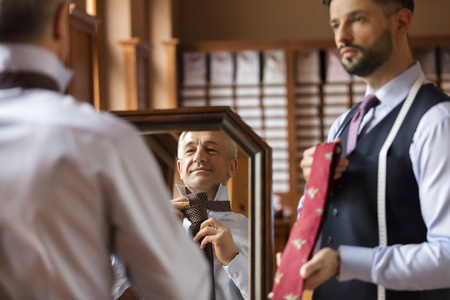 Tailor showing ties to businessman at mirror in menswear shop