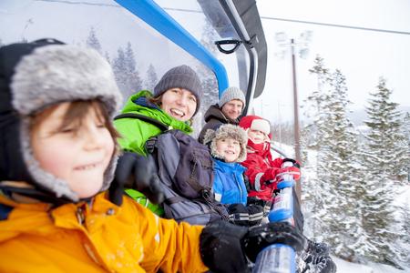 kids at the ski lift: Portrait family riding ski lift