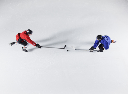 padding: Overhead view hockey opponents going for the puck on ice LANG_EVOIMAGES