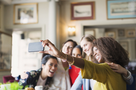 lady on phone: Smiling women friends taking selfie with camera phone in restaurant LANG_EVOIMAGES