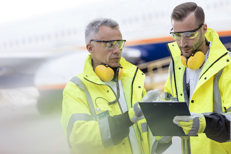 traffic controller: Air traffic controllers with clipboard talking on airport tarmac