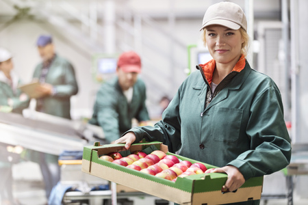 le cap: Portrait confident female worker carrying box of apples in food processing plant
