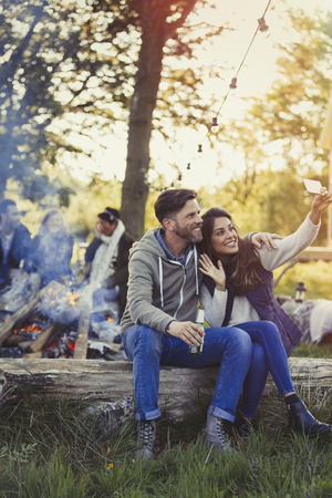 lady on phone: Couple posing for selfie with camera phone near campfire