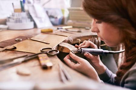 Serious focused female jeweler using equipment in workshop
