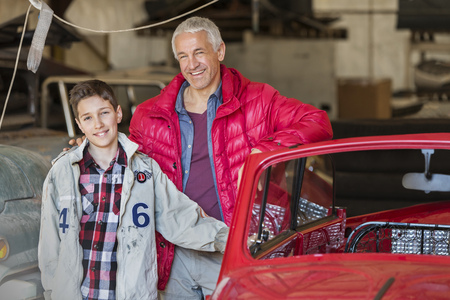 Portrait smiling father and son next to classic car in auto repair shop