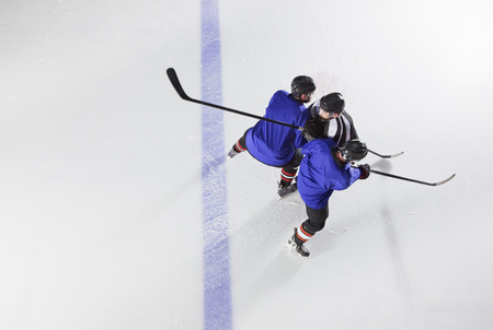 Hockey players blocking opponent on ice LANG_EVOIMAGES