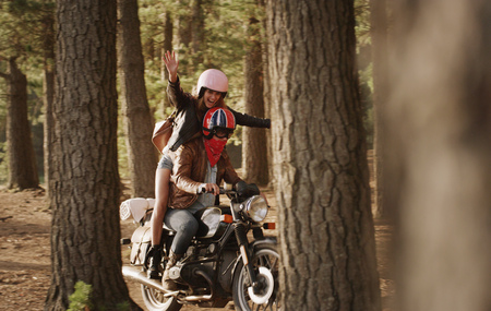 another way: Exuberant young woman riding motorcycle in woods LANG_EVOIMAGES