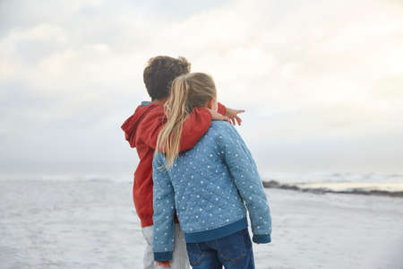 girls at the beach series: Affectionate brother and sister looking at winter ocean LANG_EVOIMAGES