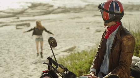 the furlough: Young man on motorcycle watching woman run onto beach