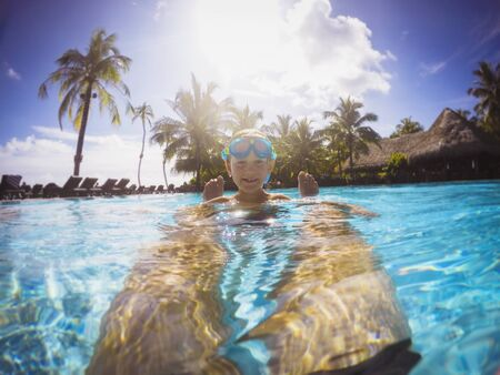 Portrait smiling boy in sunny tropical swimming pool