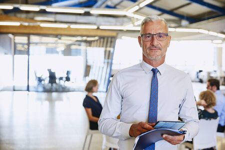 handheld device: Portrait confident businessman with digital tablet in office