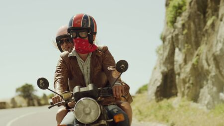 the furlough: Young couple riding motorcycle on sunny road LANG_EVOIMAGES