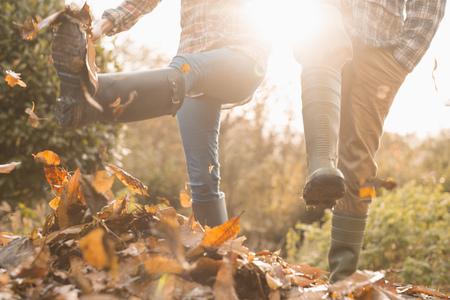 Couple in rain boots kicking autumn leaves