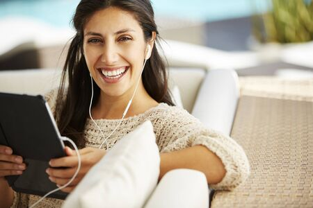 electronic book: Portrait smiling woman using digital tablet and headphones on sofa
