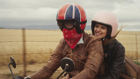 unworried: Young couple riding motorcycle in rural countryside