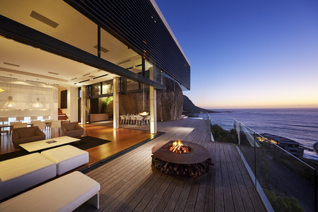 Fire pit on modern luxury home showcase beach house at sunset LANG_EVOIMAGES