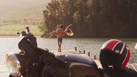 unworried: Young man carrying exuberant woman on lakeside dock behind motorcycle