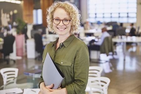 successfulness: Portrait smiling businesswoman in office