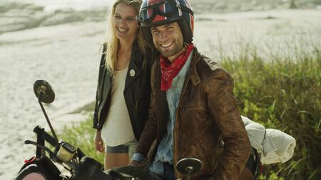Portrait smiling young couple at motorcycle on beach