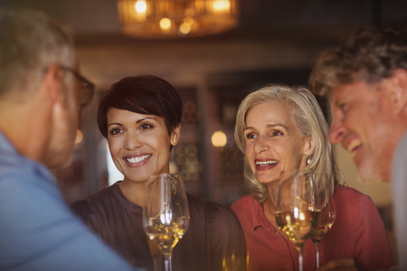 smile close up: Couples drinking white wine and talking at bar LANG_EVOIMAGES