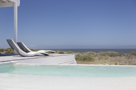 Swimming pool and modern lounge chairs overlooking ocean view under sunny blue sky LANG_EVOIMAGES