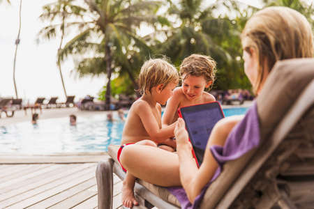 usefulness: Mother and sons relaxing with digital tablet at poolside LANG_EVOIMAGES