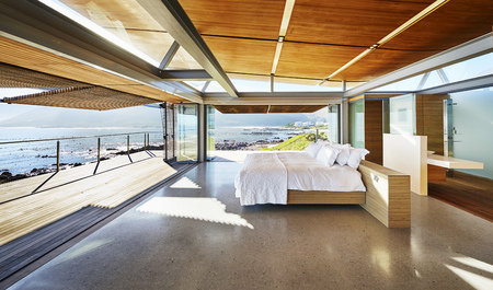 hotel bedroom: Modern luxury home showcase bed open to patio with sunny ocean view