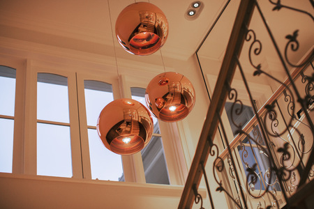 Copper pendant lights hanging over staircase