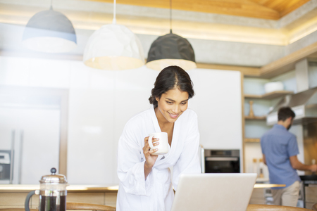 french ethnicity: Woman in bathrobe drinking coffee and using laptop in kitchen LANG_EVOIMAGES