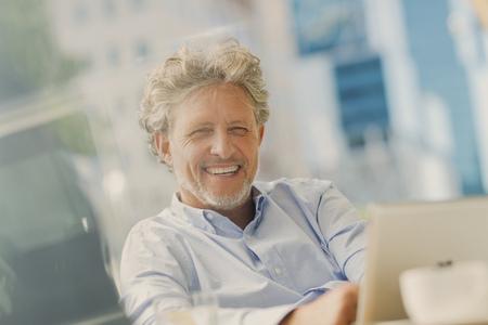 silver surfer: Portrait smiling businessman using digital tablet at sidewalk cafe