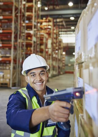 Portrait smiling worker using scanner scanning boxes in distribution warehouse