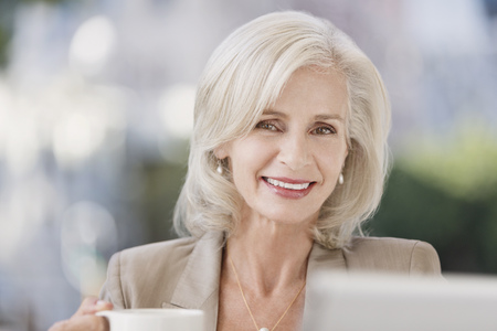 silver surfer: Portrait smiling senior businesswoman drinking coffee
