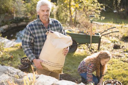 Portrait couple gardening holding potting soil in autumn garden