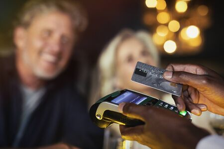 technology transaction: Close up couple paying waiter with credit card reader