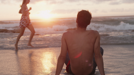 feet naked: Young man watching woman running in ocean surf at sunset