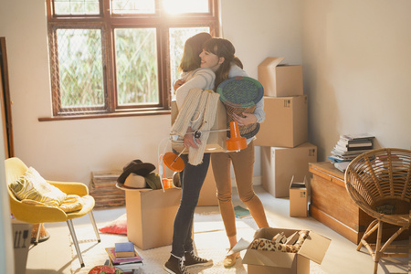 convivencia familiar: Mother and daughter hugging unpacking boxes in apartment