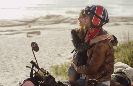 Young couple hugging at motorcycle looking at ocean view