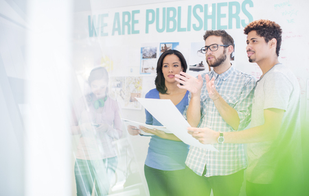 publishers: Publishers reviewing and discussing proofs in office
