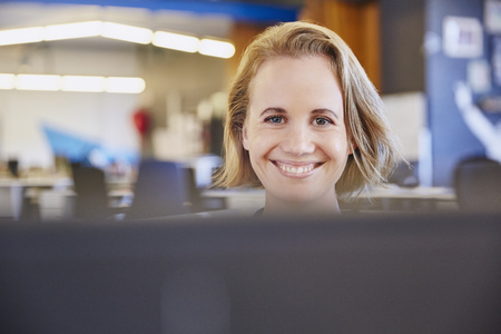 tight focus: Portrait smiling businesswoman working at computer