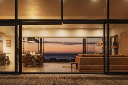 outdoor lighting: Illuminated home showcase interior overlooking ocean at sunset