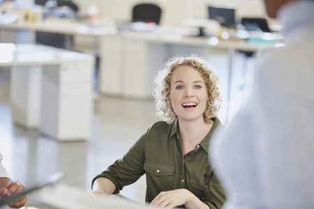Smiling businesswoman listening in meeting LANG_EVOIMAGES