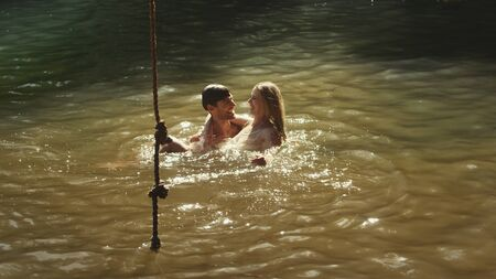 unworried: Young couple swimming in sunny lake LANG_EVOIMAGES