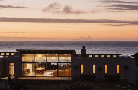 Illuminated luxury home overlooking ocean at sunset
