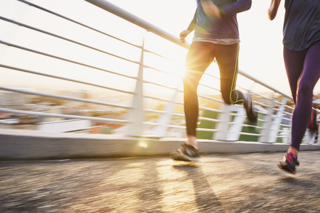 life partners: Runner couple running on sunny urban footbridge at sunrise LANG_EVOIMAGES