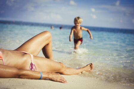 unworried: Son running toward mother sunbathing on sunny tropical beach